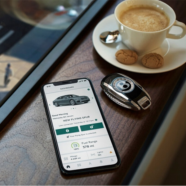 close up of smartphone next to a bentley key car and a capuccino. The smartphone is showcasing My Bentley app on the screen