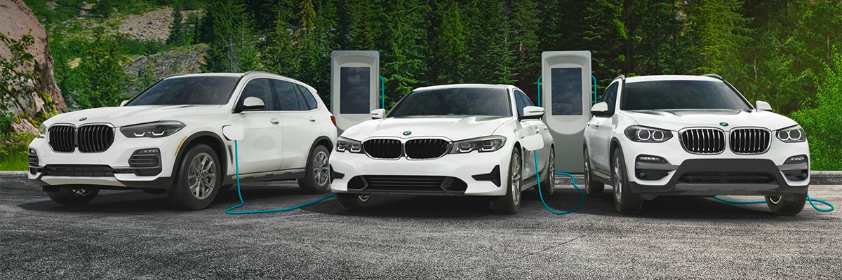 BMW X3 xDrive30e Sports Activity Vehicle®, 330e Sedan, and X5 xDrive45e SAV charging in front of bottom of mountain