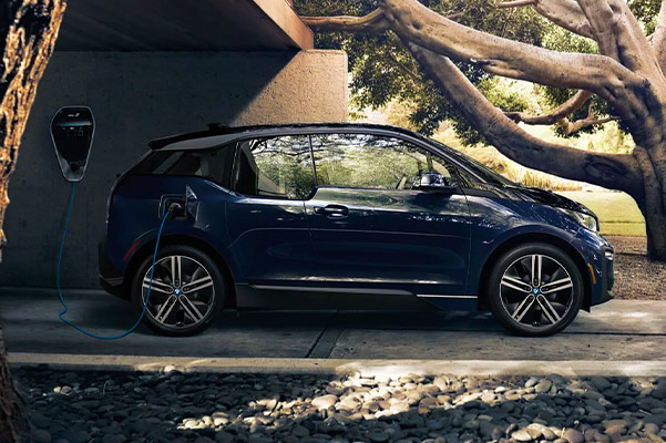 side profile view of 2020 BMW i3 charging on a driveway
