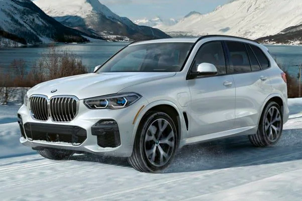 Front shot of 2021 BMW X5 xDrive45e driving through the snow