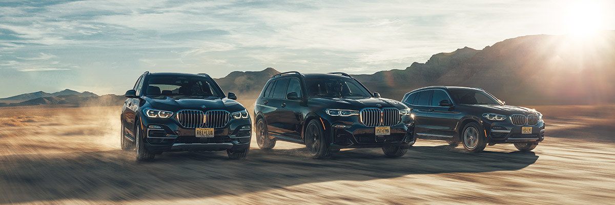 BMW suv line up accelerating in the middle of a desert