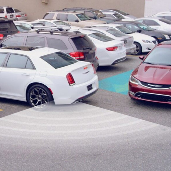 white chrysler vehicle showcasing rear cross path detection while getting out of a parking lot