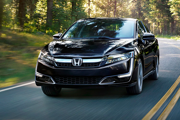 2020 Honda Clarity Plug-In Hybrid driving down road shown in black.
