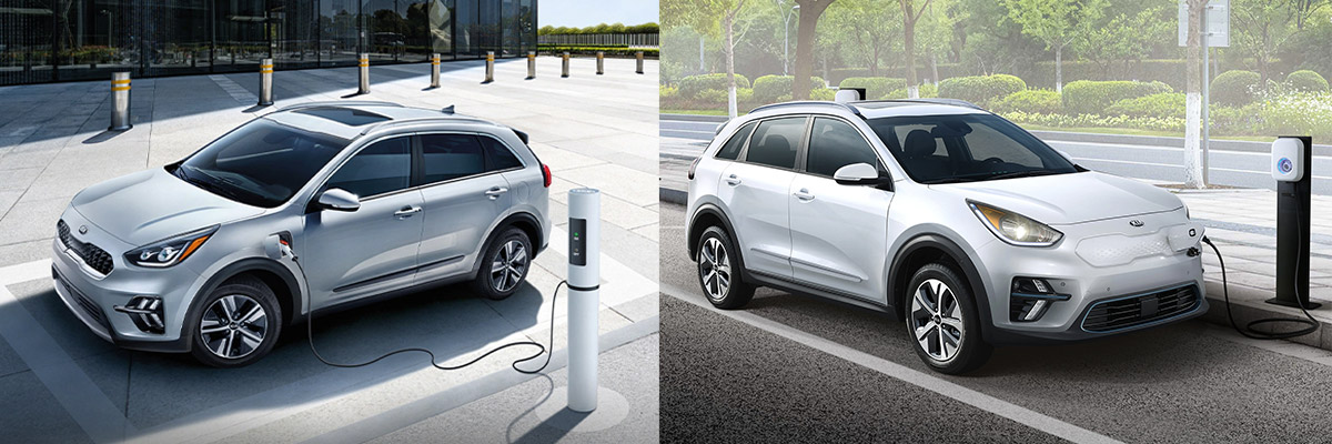 white kia Niro Hybrid and white kia Niro EV crossover getting charged from an electrical outlet on the side of a street