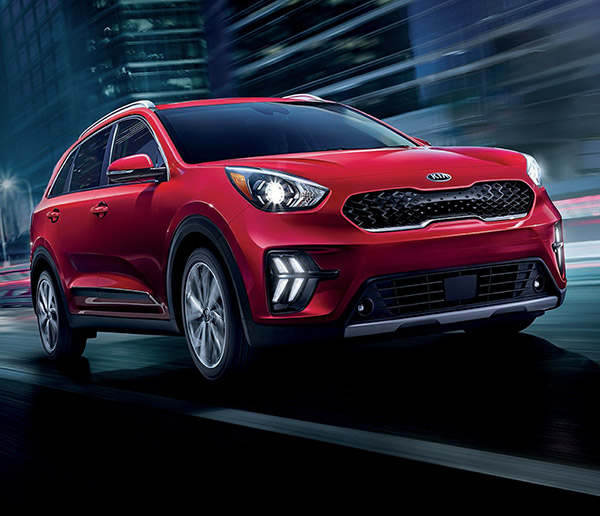 frontal profile of red 2021 kia Niro hybrid crossover driving with headlights on at high speed on a city street at night time