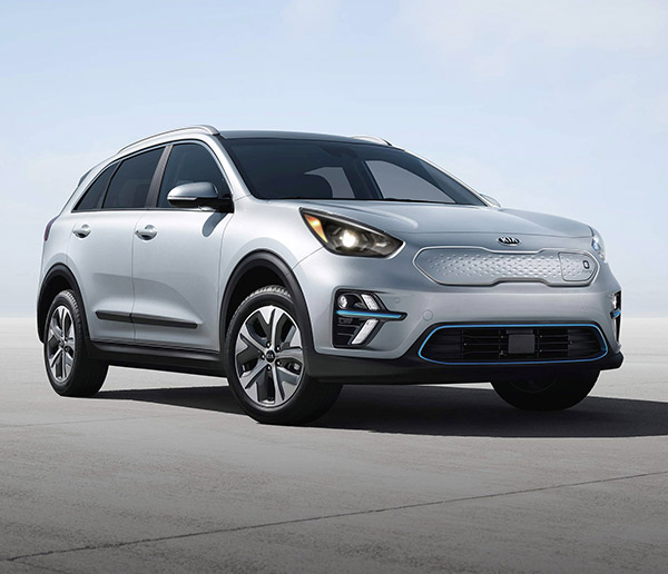 frontal profile of silver 2021 kia Niro EV electric crossover parked on a concrete floor and empty light blue sky in the background