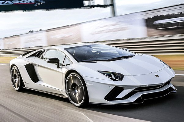a white Lamborghini Aventador sedan taking a turn on a race track