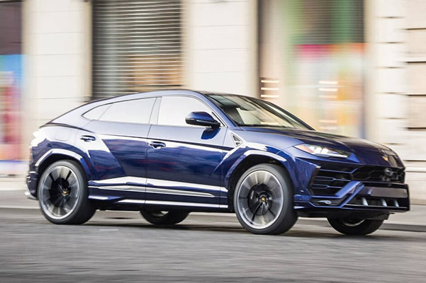 blue Lamborghini Urus suv on the road cruising through the streets