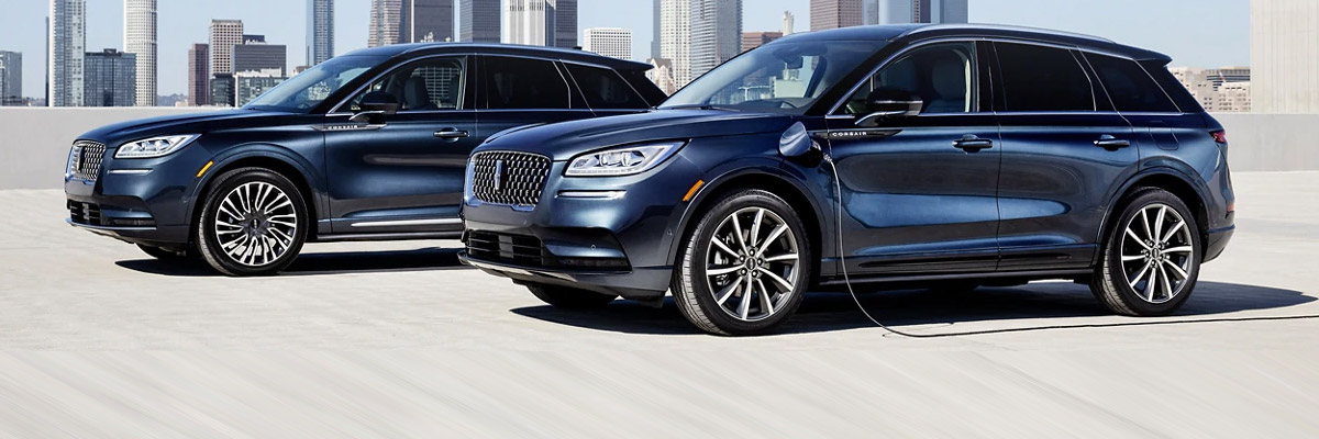 a blue 2021 lincoln aviator hybrid next to a blue 2021 lincoln corsair hybrid parked on the top floor of a parking garage building with city buildings on the horizon