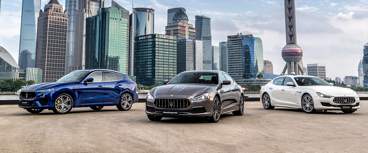 maserati model line up parked in front of a city in the background