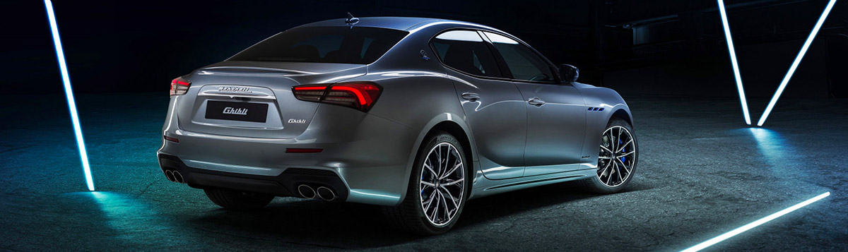 rear side view of maserati ghibly hybrid sitting on concrete against a dark studio background