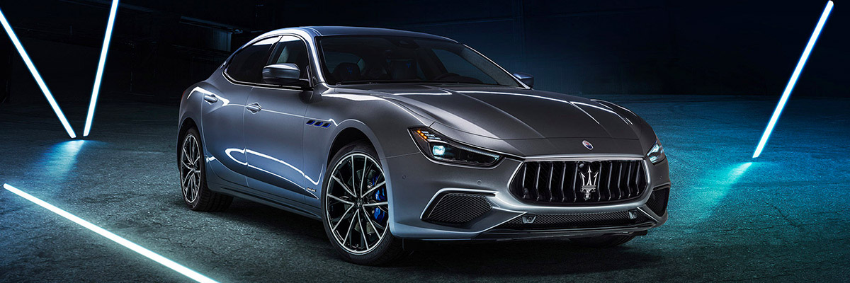 side profile of maserati ghibli hybrid sedan parked on concrete against a dark studio background