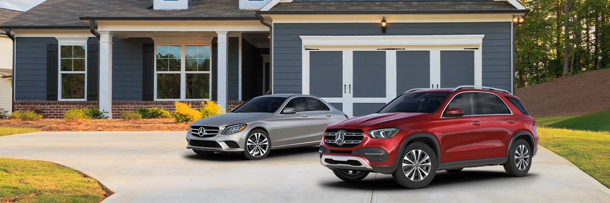 silver Mercedes-Benz C class sedan and red Mercedes-Benz GLE suv parked outside of a house on the driveway