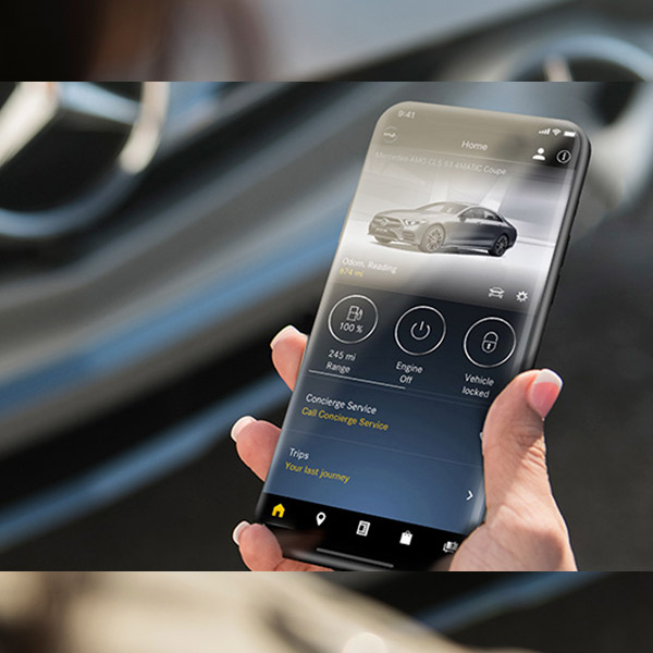 A hand holding a phone with the Mercedes me app on-screen, and a Mercedes-Benz S-Class Sedan in the background.