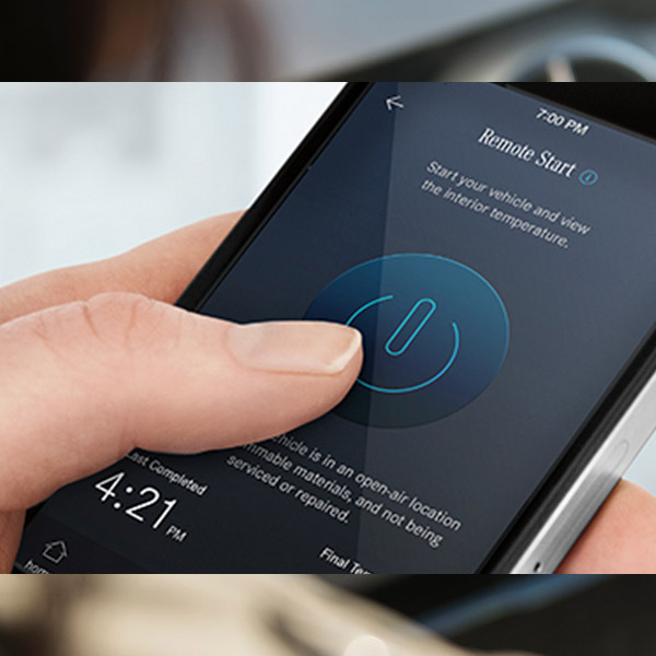 A hand holding a phone, about to press the Remote Start button on the Mercedes me app.  Notes