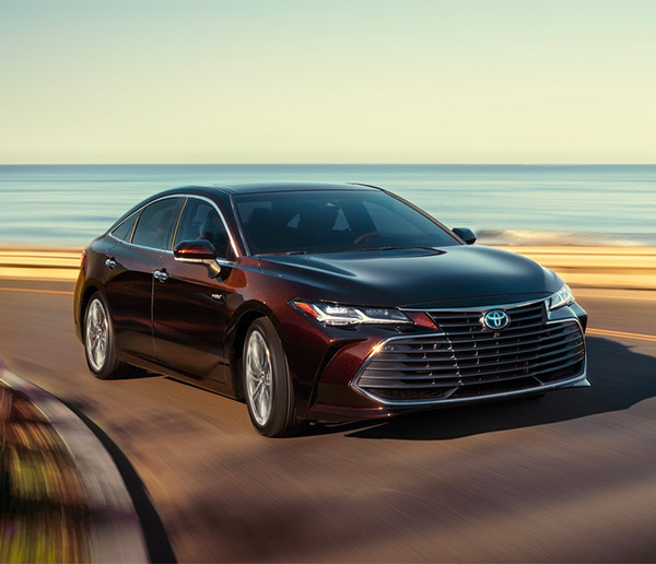dark red toyota avalon hybrid taking a curve on the road with the a ocean in the background