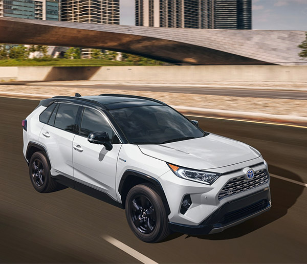 frontal sideview of white toyota rav4 hybrid on the road traveling at a high speed