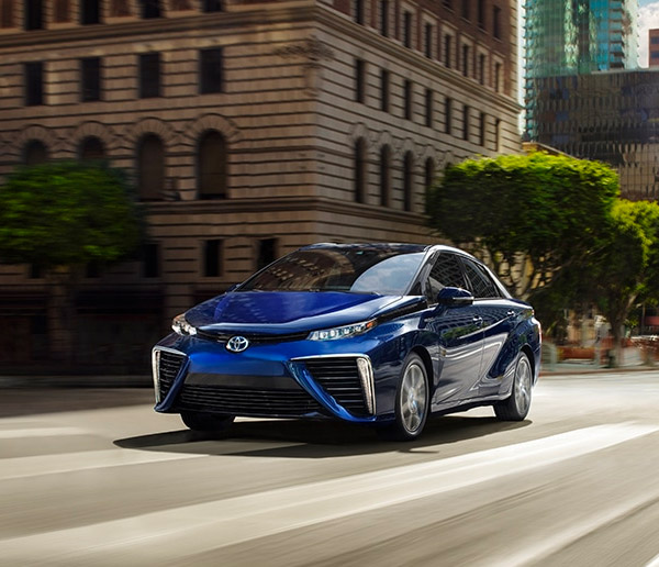 blue toyota Mirai accelerating on the road sorrunded by commercial buildings